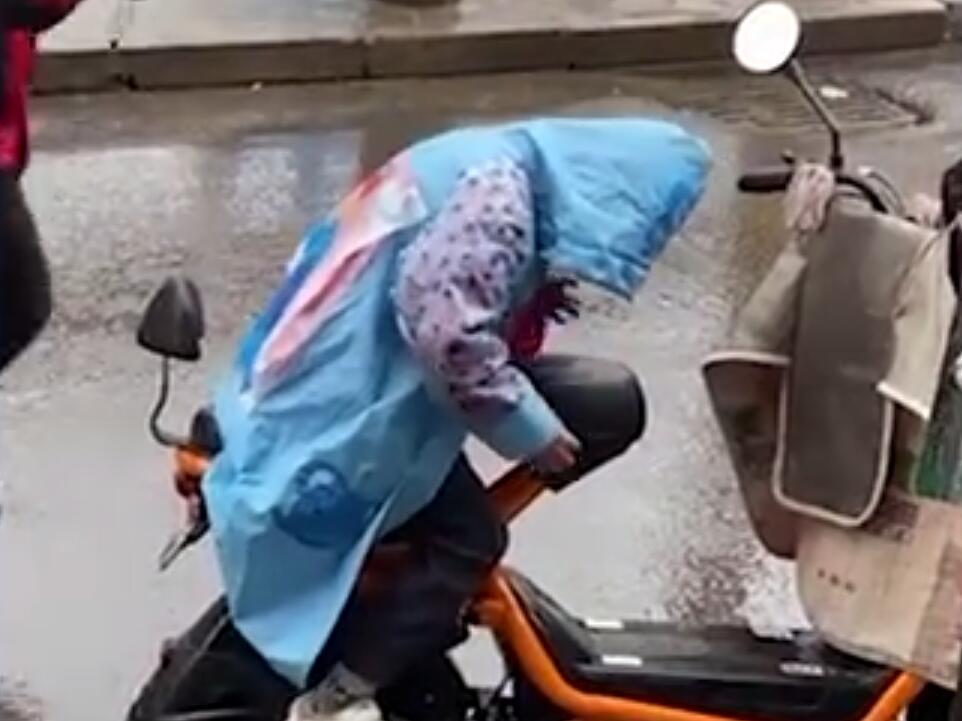 孩子用身体给妈妈电动车座位挡雨